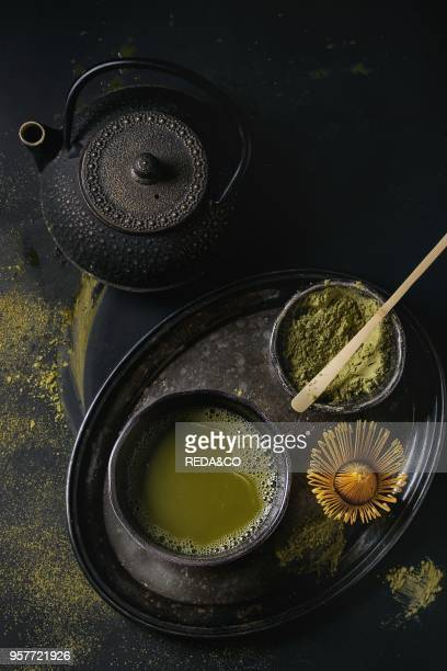 Green tea matcha powder and hot drink in black bowls standing with iron teapot bamboo traditional tools spoon and whisk in vintage tray over dark...