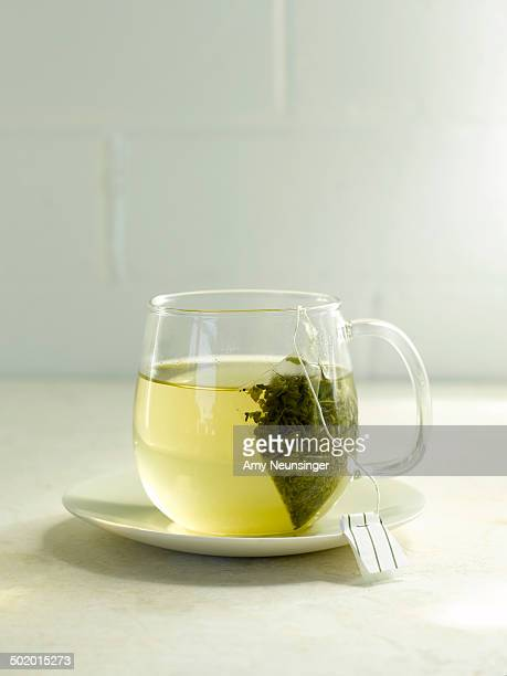 Green tea steeping in clear glass mug on plate.