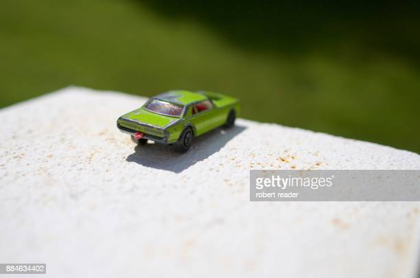 Green toy car on the edge of a wall