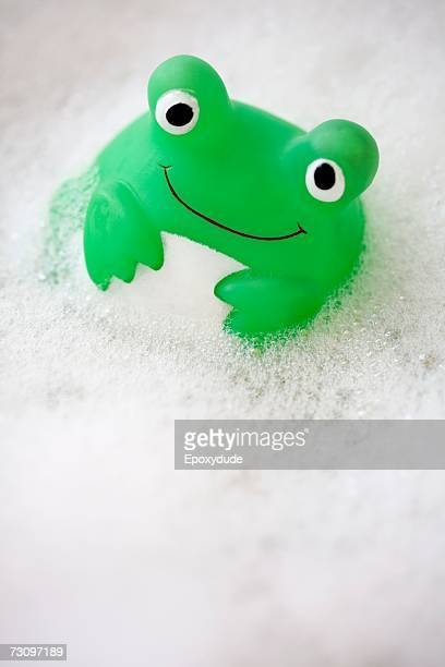 Green toy floating in bubble bath