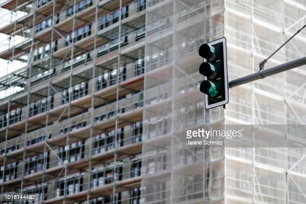 BERLIN GERMANY AUGUST Green traffic lights in front of a building with scaffolds of house construction are pictured on August 10 2018 in Berlin...