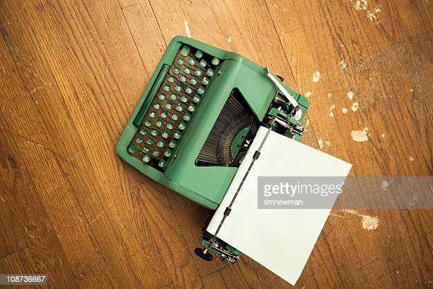Green Typewriter on Hardwood Floor