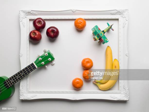 Green ucalaly colourfully displayed alongside fruit and a toy green airplane within a white picture frame on a white background