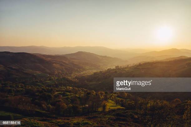 green valley at sunset - resplandeciente stock pictures, royalty-free photos & images