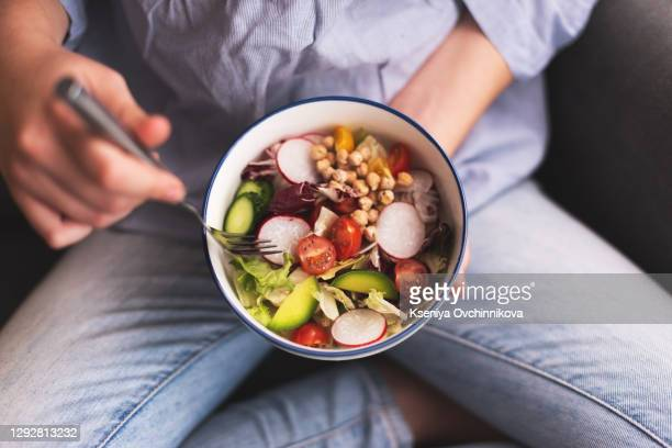 green vegan breakfast meal in bowl with spinach, arugula, avocado, seeds and sprouts. girl in leggins holding plate with hands visible, top view. clean eating, dieting, vegan food concept - vegetarian food stock pictures, royalty-free photos & images