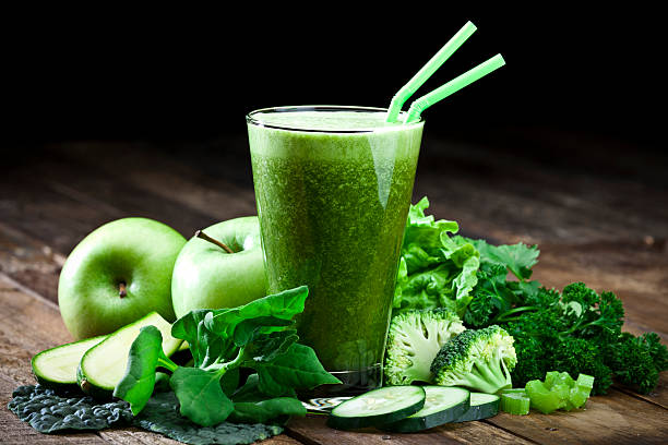 Green vegetable juice on rustic wood table