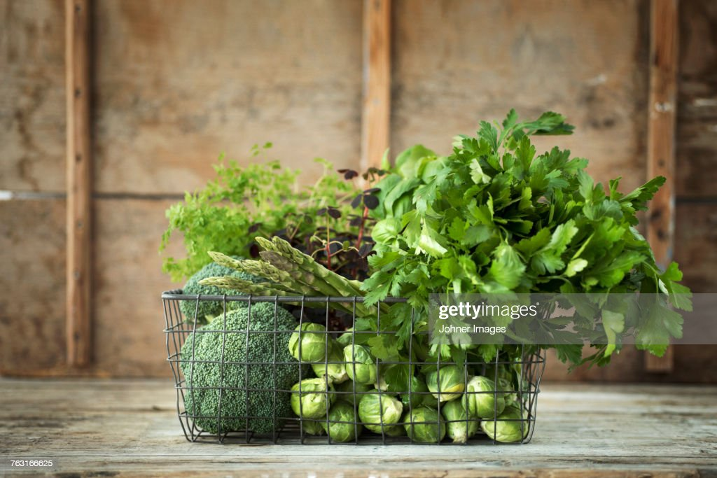Green vegetables and herbs in wire basket : Stock Photo