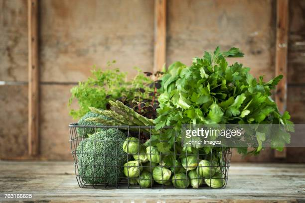 green vegetables and herbs in wire basket - crucifers stock pictures, royalty-free photos & images