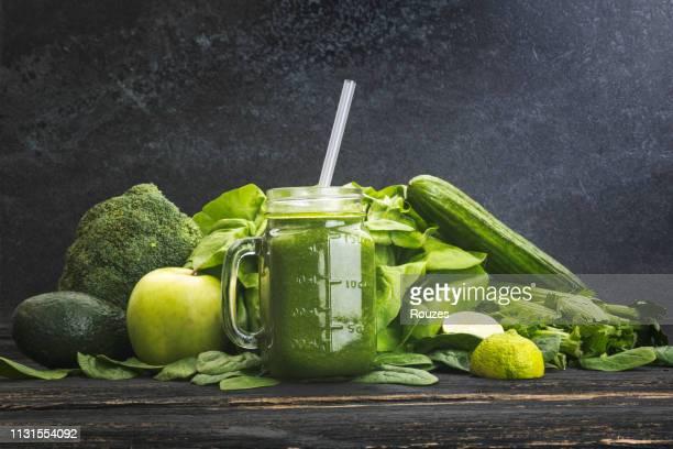 verduras verdes y jugo sobre fondo oscuro - apio fotografías e imágenes de stock