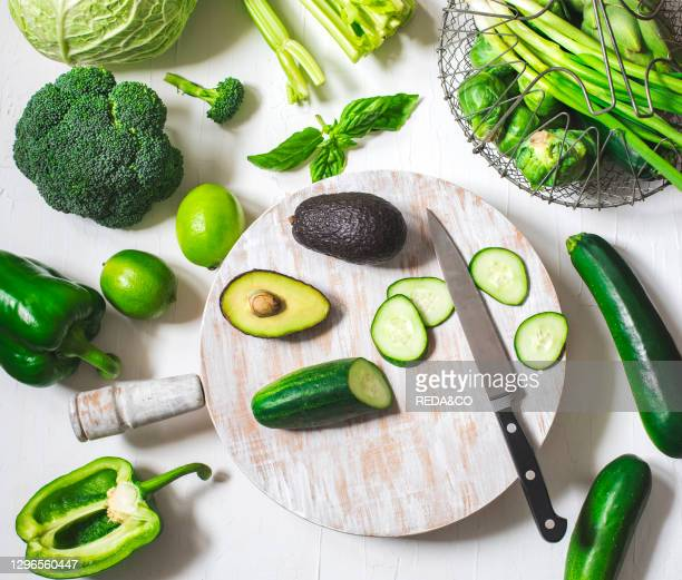 Green vegetables on a wooden cooking board. Healthy food. Top view.