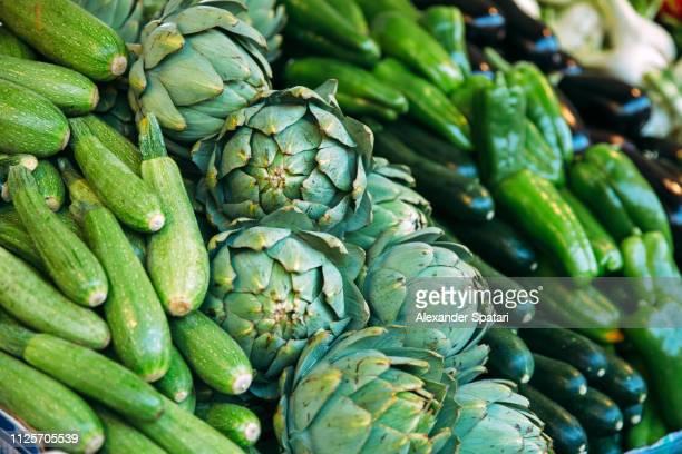 green vegetables - zucchini, artichoke, cucumbers and green pepper on the market stall - foco diferencial imagens e fotografias de stock