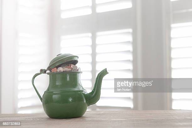 Green vintage teapot full of British coins on table