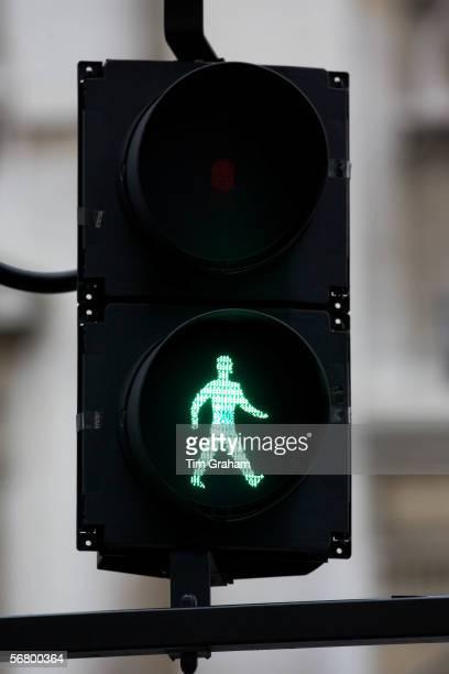 Green walk symbol on pedestrian crossing lights London United Kingdom