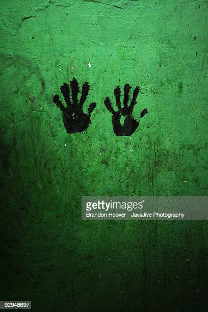 Green wall with black handprints; both left handed
