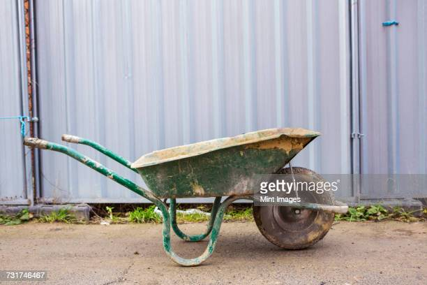 green wheelbarrow on a building site in front of a metal container. - wheelbarrow stock photos and pictures