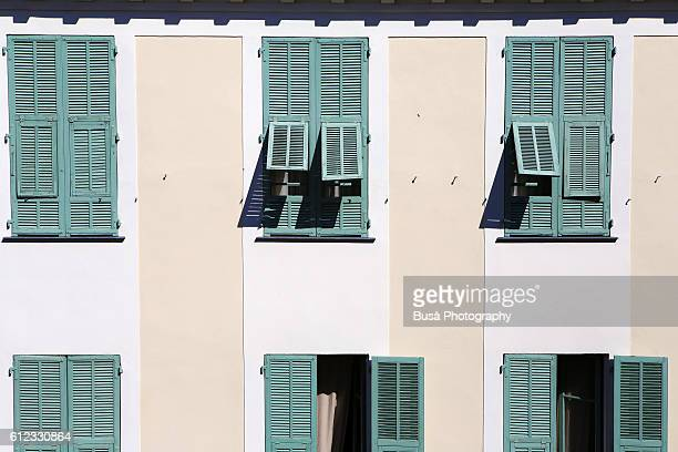 Green window shutters in old residential building in Nice, France