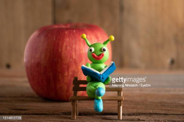 green worms are made of plasticine and apple.cartoon style worm.bookworm concept. - clay stock pictures, royalty-free photos & images