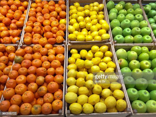 green, yellow and orange. apples, lemons and tangerines - lemon fruit stock pictures, royalty-free photos & images