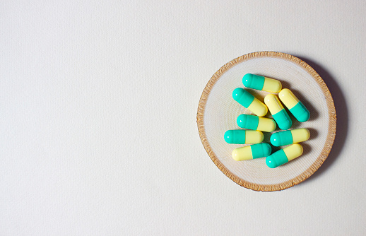 Green yellow pills or capsules stack freely on a wooden circle on a light background. 1225457868