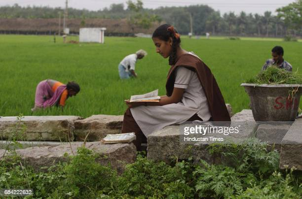 Greenacres Aishwarya studies for her Tenth Boards from her anthology of Tamil classics in salwarkameez school uniform while her brother Ram Kumar and...