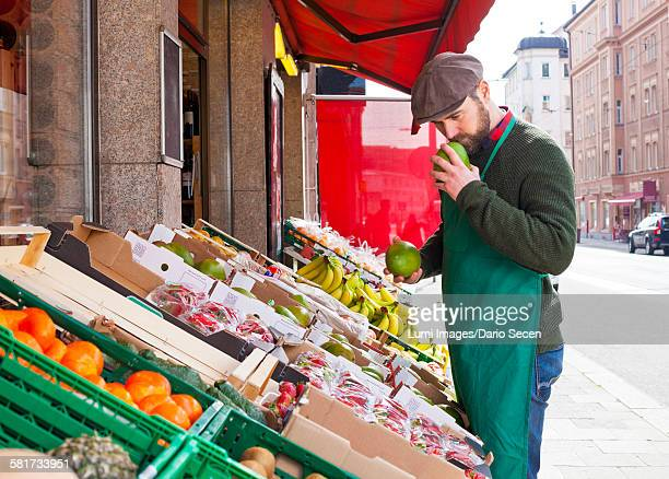 Greengrocers shop, grocer smelling fruit