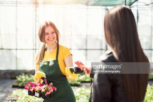 greenhausarbeiter verkaufen topfblumen. kontaktlose kartenzahlung. - zahlen stock-fotos und bilder