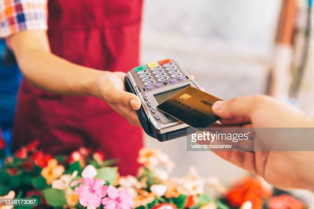 greenhouse workers selling pottered flowers.contactless payment with credit card - suit stock pictures, royalty-free photos & images