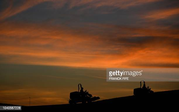 Greenkeepers ride on lawnmowers as the sun rises before players take part in a practice session ahead of the 42nd Ryder Cup at Le Golf National...