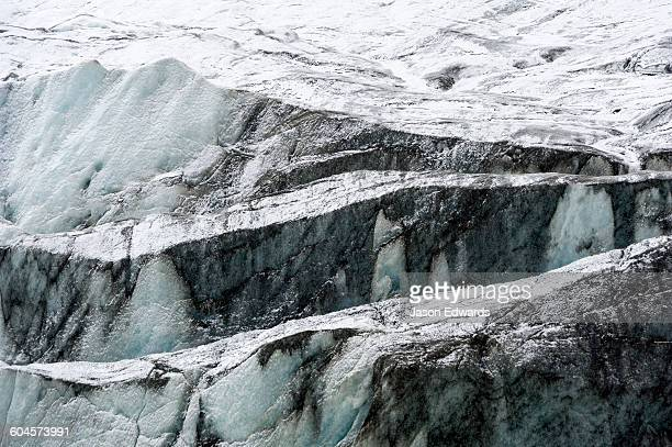 Silt and sediment darkens the surface of a glacier where its eroding the surrounding rock.
