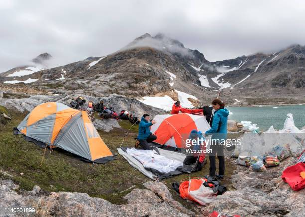 greenland, sermersooq, kulusuk, schweizerland alps, group of people setting up camp - base camp stock pictures, royalty-free photos & images
