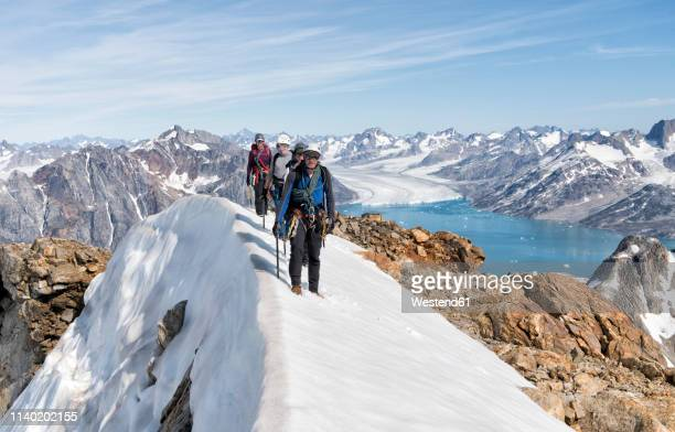 greenland, sermersooq, kulusuk, schweizerland alps, mountaineers walking in snowy mountainscape - mountain ridge stock pictures, royalty-free photos & images