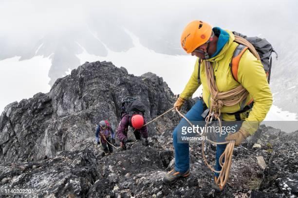 greenland, sermersooq, kulusuk, schweizerland alps, mountaineers with rope ascending rocky mountain - betrouwbaar stockfoto's en -beelden
