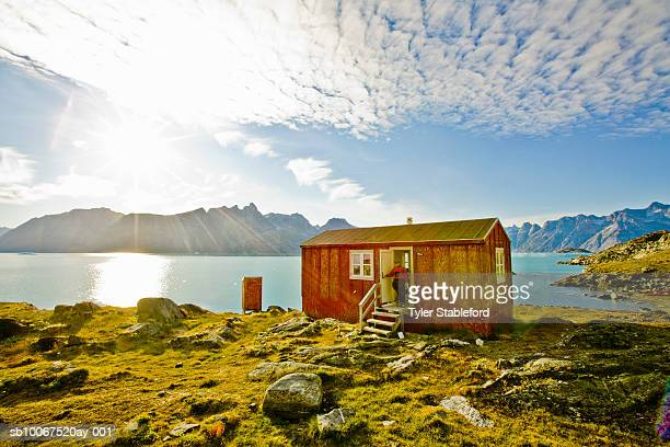 Greenland, Tasiilaq, man walking out of public camping hut