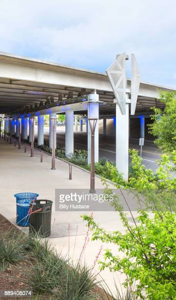 A green-leaf landscaped setting under a concrete highway overpass with garbage and recycling bins
