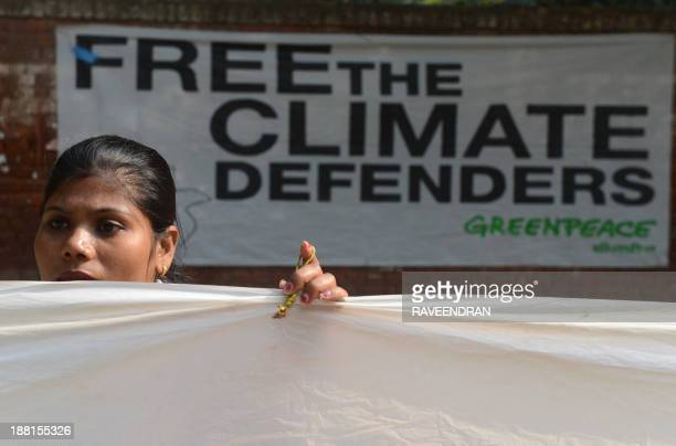A Greenpeace activist demonstrates during a 30hour long protest in New Delhi on November 16 to demand the release of a group of Greenpeace activists...