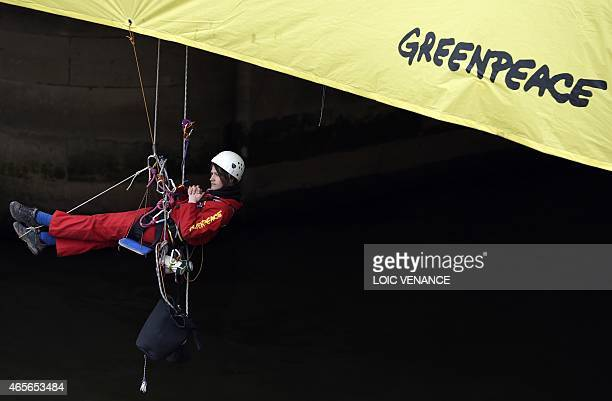 A Greenpeace activist displays a banner on the Concorde bridge in front of the French National Assembly in Paris on March 9 2015 The banner was hung...