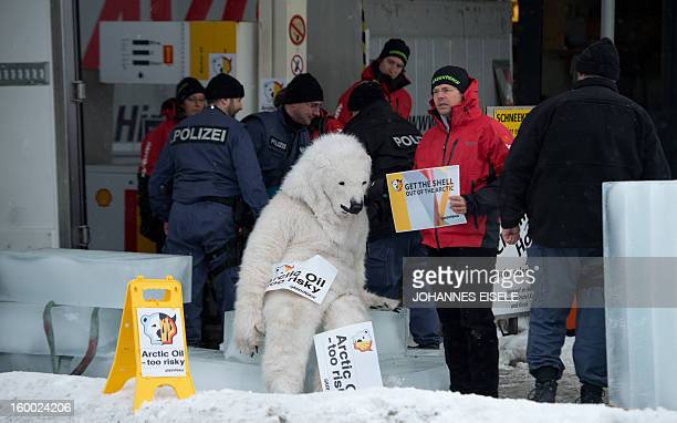 A Greenpeace activist dressed as a polar bear is chained onto a petrol tap at a filling station during a protest against global oil giant Shell on...