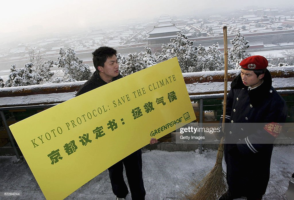 A Greenpeace activist holds up a sign supporting the Kyoto protocol on February 16, 2005 in Beijing, China. Greenpeace offices around the world celebrate the coming into force of the protocol today. After more than ten years of protracted negotiations, thirty five industrialised countries along with the European Community are now legally bound to reduce or limit their greenhouse gas emissions.