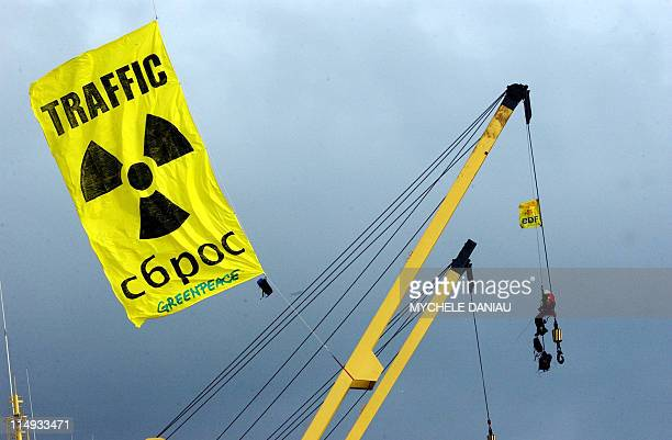 A Greenpeace activist is pictured trying to prevent the departure with some 20 other activists of a cargo loaded with nuclear waste a few moments...
