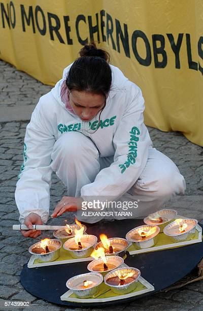 Greenpeace activist lights candles next to a banner reading No more Chernobyls during a protest against the usage of nuclear power reactors similar...