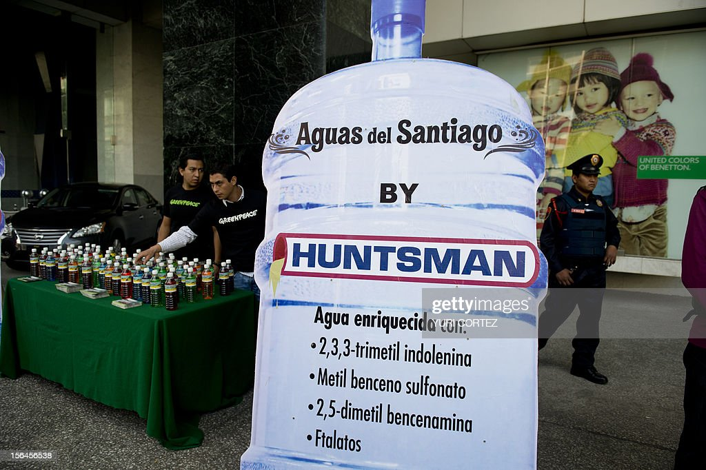 A Greenpeace activist prepares to distribute coloured water bottles labeled 'Huntsman-Waters from the Santiago', during a protest at the World Trade Center against Huntsman Corporation on November 15, 2012 in Mexico City. According to a statement distributed by Greenpeace, Huntsman, one of the largest suppliers of chemicals for the textile sector globally, discharges pollutants into the Rio Santiago in Jalisco, Guadalajara, which affect the human health and the aquatic ecosystem.