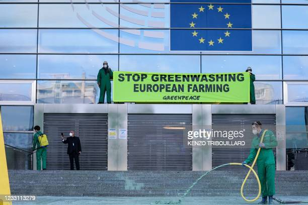 Greenpeace activist sprays green-coloured water at the entrance of the European Parliament in Brussels on May 26, 2021. - Greenpeace accuse the...