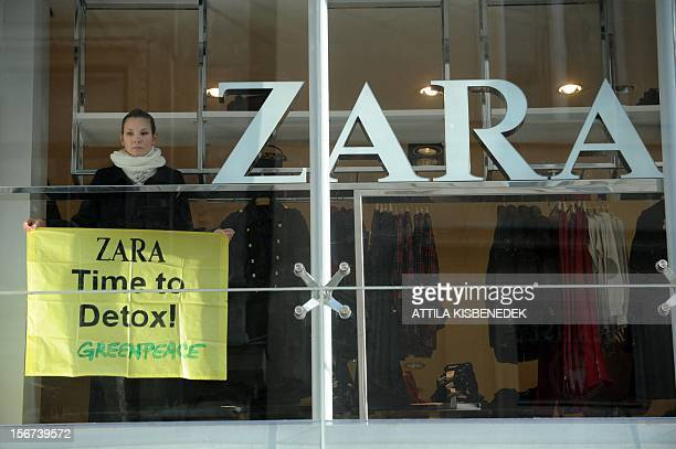 A Greenpeace activist stands with her banner in the window of Zara's fashion shop in Budapest on November 20 2012 during a demonstration High street...