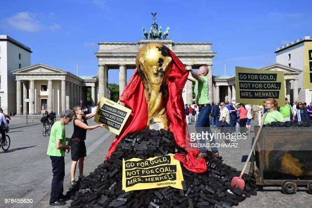 TOPSHOT Greenpeace activist unveil a mockup of the Football World Cup trophy standing on a pile of coal briquettes as they stage a demonstration...