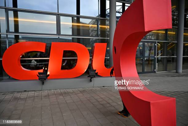 """Greenpeace activist walks in front of the congress hall with the letter """"C"""" of the logo of the CDU party as part of an action for climate before the..."""