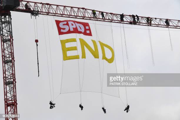 "Greenpeace activists abseil from a crane with the logo of Germany's social democratic SPD party and the lettering ""END"" close to the venue of an..."