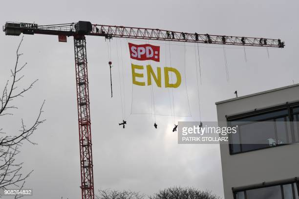 Greenpeace activists abseil from a crane with the logo of Germany's social democratic SPD party and the lettering 'END' close to the venue of an...