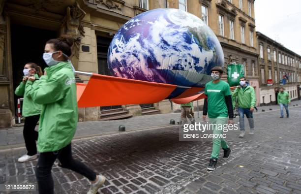 Greenpeace activists carry on a stretcher a giant balloon representing planet Earth which is connected to an infusion to the Croatian parliament, in...