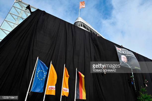 Greenpeace activists entirely wrap the party headquarters of the Christian Democratic Union with black fabric to protest against the party's politics...