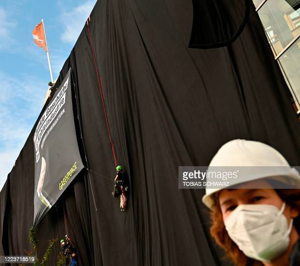 Greenpeace activists entirely wrap the party headquarters of the Christian Democratic Union with black fabric and attach a poster featuring German...